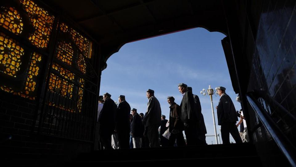 Uighur men make their way past a subway entrance after Eid-ul-Fitr prayers, marking the end of Ramzan, at the Idkah mosque in Kashgar, in China's Xinjiang region. While Muslims around the world celebrated the end of Ramzan with prayers and festivities, the recent destruction of dozens of mosques in Xinjiang highlights the increasing pressure Uighurs and other ethnic minorities face in the heavily policed region. (Greg Baker / AFP)
