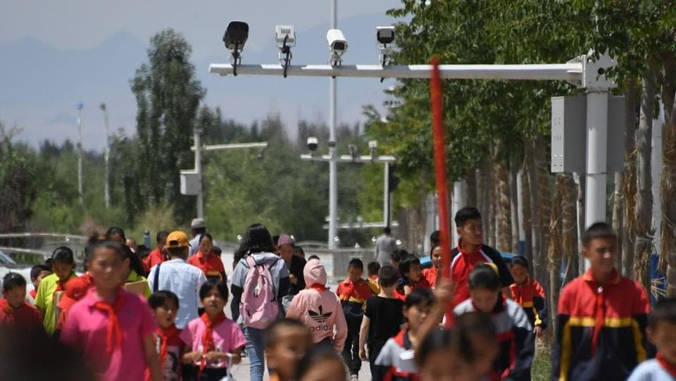 Schoolchildren walk below surveillance cameras in Akto, south of Kashgar. Authorities have thrown a high-tech security net across the region, installing cameras, mobile police stations and checkpoints in seemingly every street in response to a spate of deadly attacks blamed on Islamic extremists and separatists in recent years. (Greg Baker / AFP)