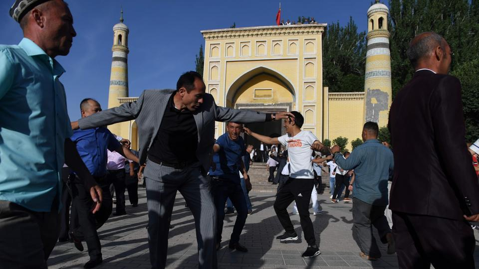 "Men dance after the Eid-ul-Fitr prayers at Idkah mosque. Uighurs consider mosques and shrines ""their ancestral heritage,"" said Omer Kanat, director of the Uyghur Human Rights Project. ""The Chinese government just wants to erase everything... that is different from Han Chinese, everything which belongs to Uighur culture or Islamic culture in the region,"" he added. (Greg Baker / AFP)"