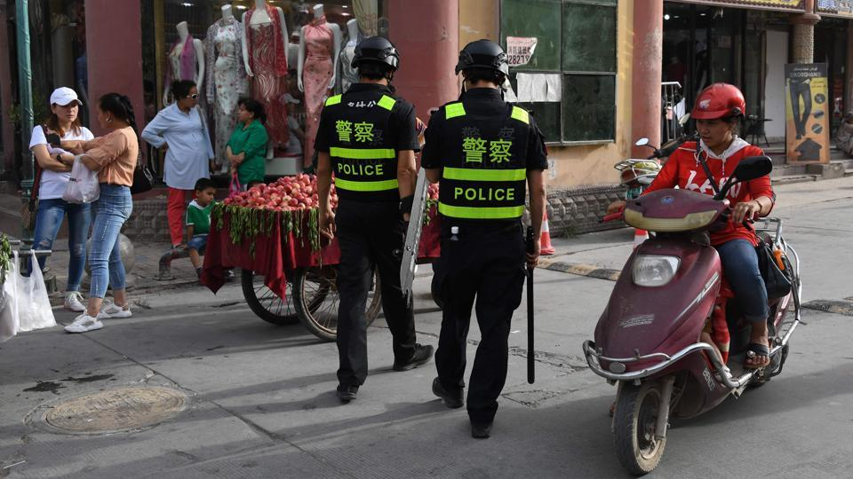 "Police officers patrol in Kashgar. At state-backed mosques, religious activity is controlled as Beijing pursues a five-year plan to ""Sinicise"" Islam as the ""only way for a healthy development of Islam"" in the country, said Yang Faming, president of the state-backed Islamic Association of China, in January. (Greg Baker / AFP)"