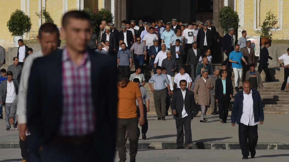 Uighur men leave after Eid-ul-Fitr prayers at Idkah Mosque in Kashgar. On Wednesday, locals celebrating Eid quietly filed into the entrance of the state-approved Idkah Mosque -- one of the largest in China -- as police and officials fenced off the wide square surrounding the building and plainclothes men monitored every person's actions. (Greg Baker / AFP)