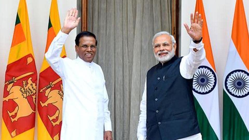 Prime Minister Narendra Modi (R) and Sri Lankan President Maithripala Sirisena wave prior to a meeting and delegation-level talks in New Delhi.