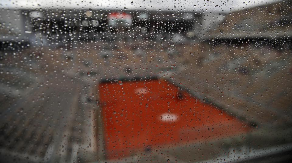Rain drops trickle down a glass wall on center court as showers interrupted the men's semifinal match.