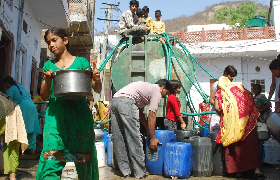 the rush of people as the water tanker reaches a colony in Jaipur.