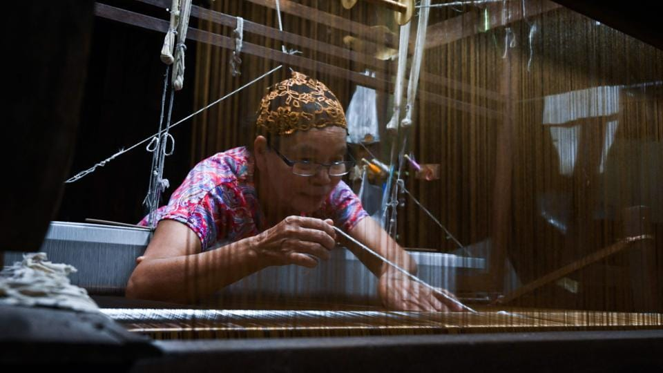 Rampai Sripetch, 65 -- weaves silk fabric on a loom at a workshop near Darul Falah mosque in Bangkok. There is a steady decline in apprentice weavers at silk shops, as modernity lures young Muslims away from a trade their community has dominated for generations. (Romeo Gacad / AFP)
