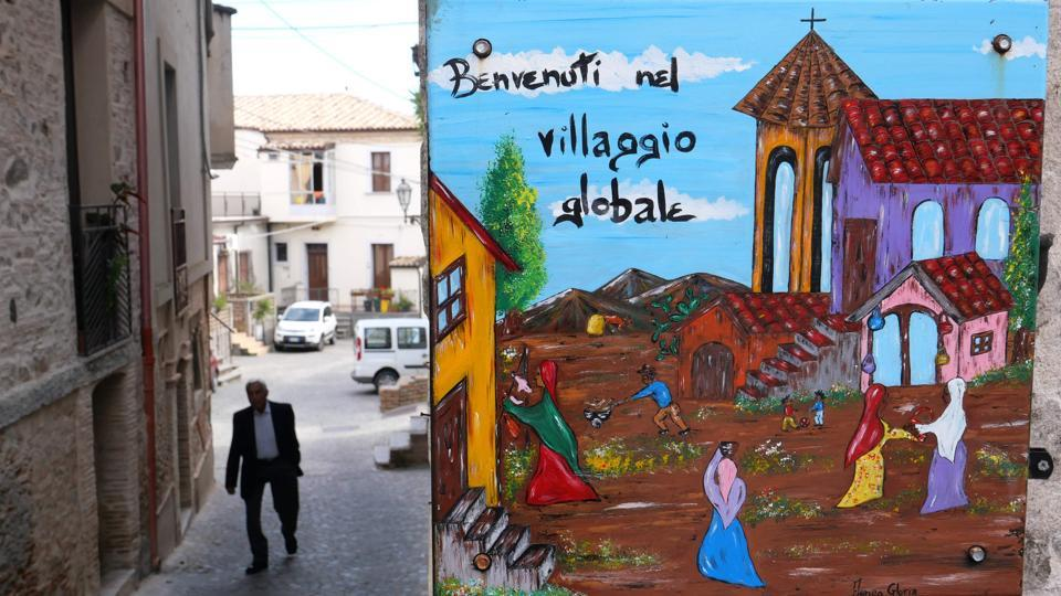 "A hand painted road sign ""Welcome to the Global Village"" still hangs in the small town, but its dream of migrant integration is over after the far-right's ""Italians first"" election victory. (Alberto Pizzoli / AFP)"