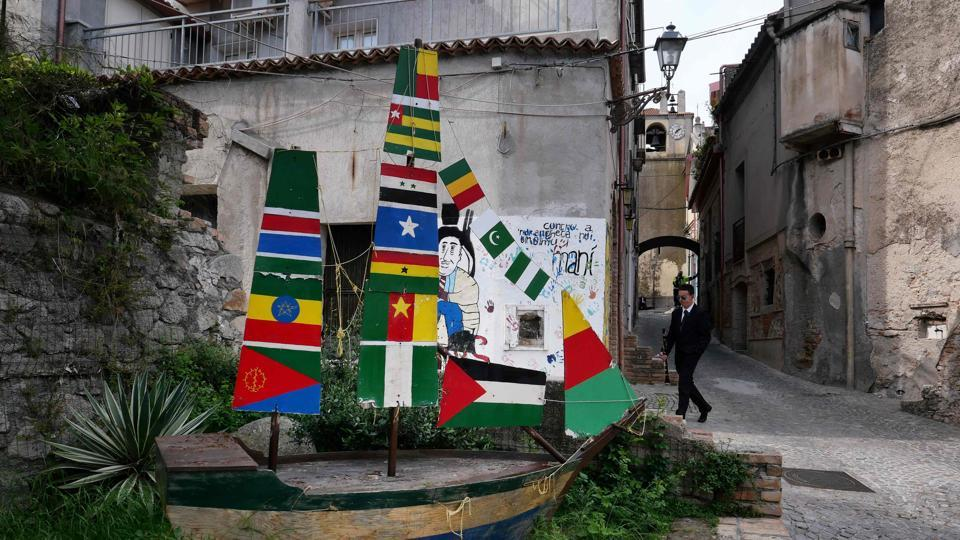 "A view of a boat sculpture with flags of various African, Middle-Eastern and Asian countries. ""We will welcome refugees again. But we can't have 500 to 600 asylum seekers in a town with 1,500 residents,"" Trifoli said. (Alberto Pizzoli / AFP)"