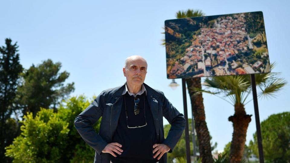 "Secretary of the Lega Nord for the Riace marina area, Claudio Falchi poses by a billboard of Riace. He moved here 25 years ago, ""Here, we need order and discipline; it's not racism, it's just that this is our home. We welcome them and then they make problems"". Until a few years ago, the Lega was a separatist party at the other end of the country which sneeringly referred to southerners as ""bumpkins"" or worse. (Alberto Pizzoli / AFP)"