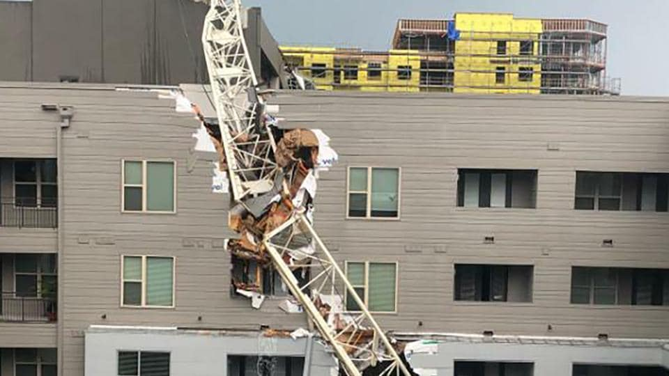The crane fell onto the Elan City Lights apartment complex, which left a large hole in the east side of the building and landed on an adjacent parking garage.