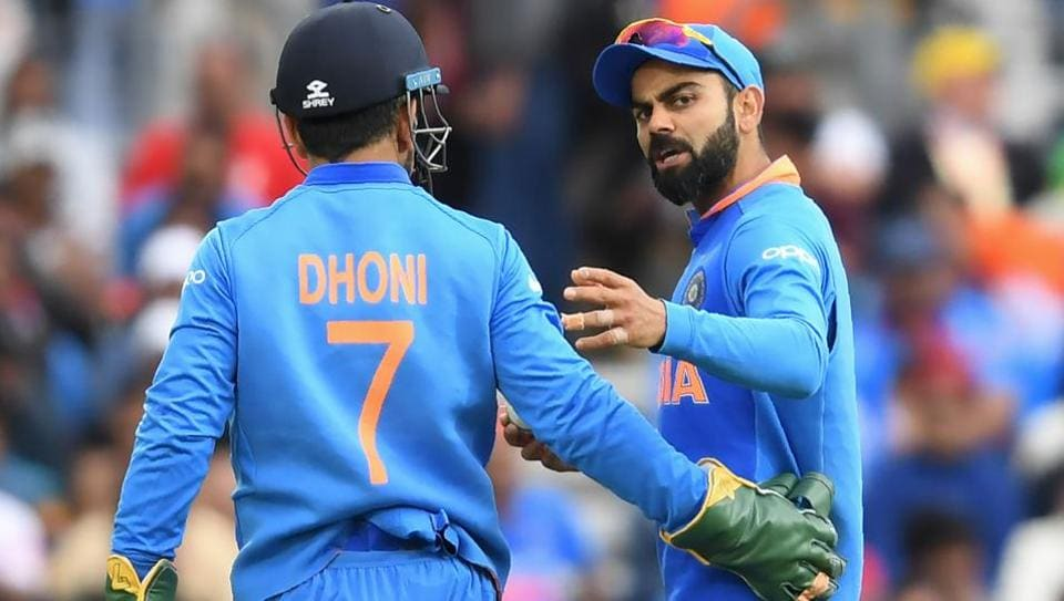 India's captain Virat Kohli (R) speaks with teammate Mahendra Singh Dhoni during the 2019 Cricket World Cup group stage match between India and Australia at The Oval