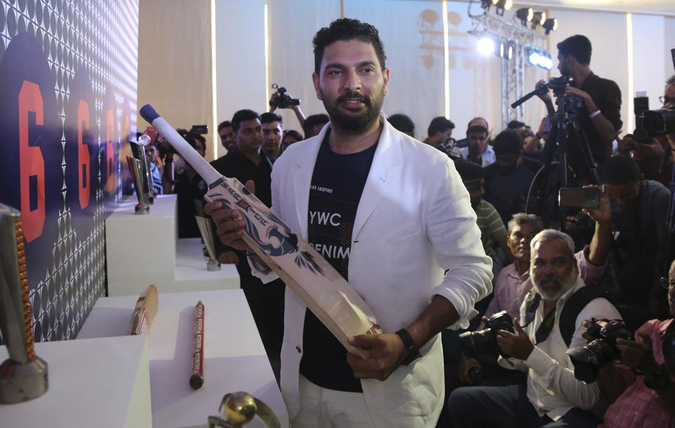 Indian cricket player Yuvraj Singh holds a bat as he poses for photographs after announcing his retirement.