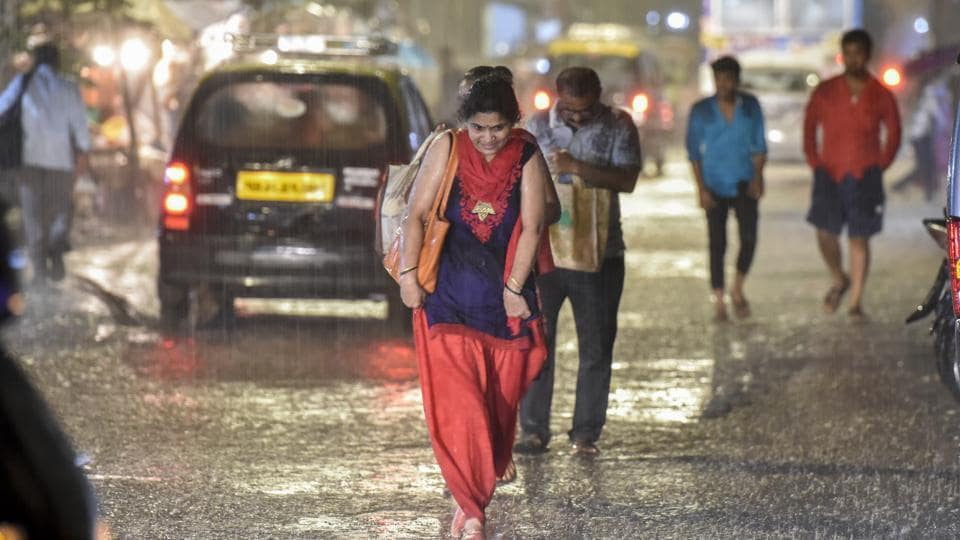 People caught in sudden heavy rain at Sion in Mumbai, on Monday, June 10, 2019.