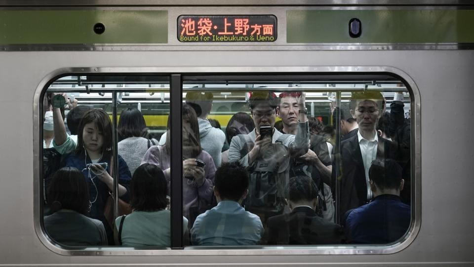 Commuters stand in a packed Yamanote Line train while waiting for the train at Shinjuku Station in Tokyo. The trains are so densely packed during morning and evening rush hours that passengers don't need to hold onto a handrail to avoid falling. There are shoves from commuters who can't wait three to four minutes for the next train, but no one growls in irritation. It's typically forgiven with a little nod, a gesture of apology. (Jae C. Hong / AP)