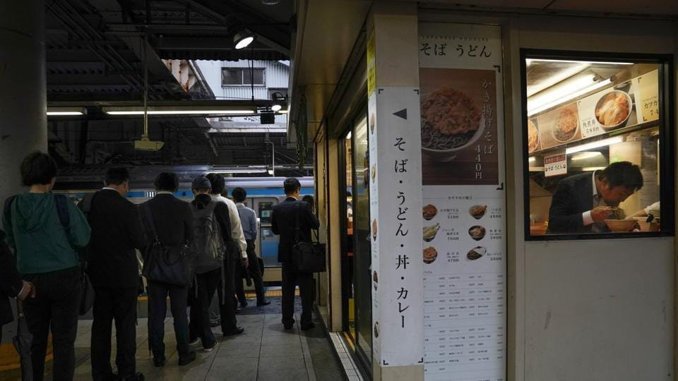 A man eats his breakfast in a noodle shop located on a platform. Eating on the train is not recommended. For a much better option, commuters get off for an authentic bowl of soba or udon, all priced under 500 yen ($5).  (Jae C. Hong / AP)