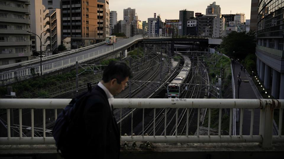 A man walk on the bridge as a Yamanote Line train departs from Ikebukuro Station in Tokyo. If a commuter misses its station, then he will return 28 stations later, or else has to get off at any stop and catch a train travelling around the loop in the opposite direction. (Jae C. Hong / AP)