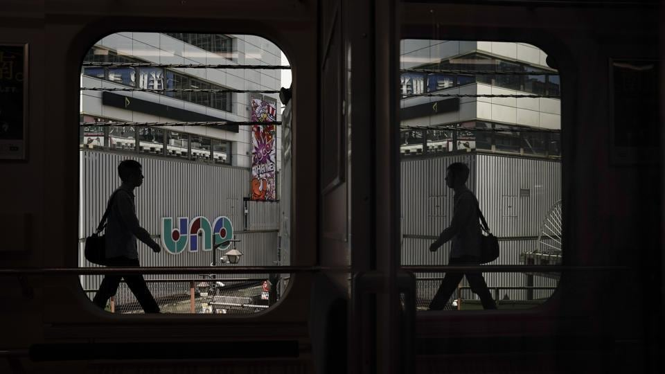 A commuter is reflected in the window of a Yamanote Line train as he gets off at Shimbashi Station in Tokyo. A complete loop of the journey in these trains for about an hour offers scenes of Japanese daily life: jam-packed commutes, views of the famous Shibuya crossing, local shopping arcades and stand-up noodle shops on train platforms.  (Jae C. Hong / AP)