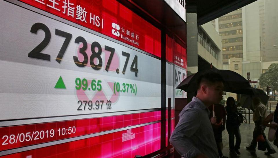 Hong Kong stocks tumbled and the currency soared as interbank interest rates jumped amid protests that closed roads in the city's financial district.