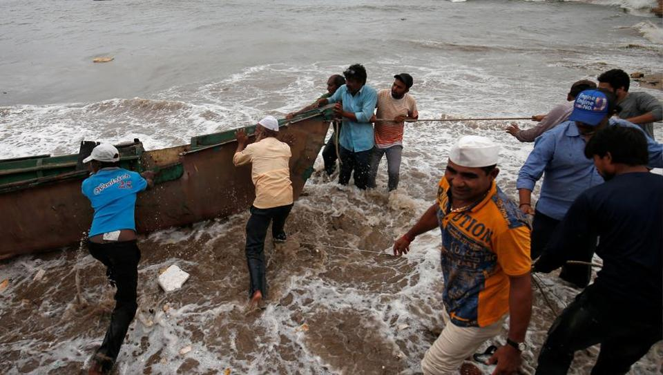 Fishermen move a fishing boat to a safer place along the shore ahead of the expected landfall of Cyclone Vayu at Veraval, India, June 12, 2019.