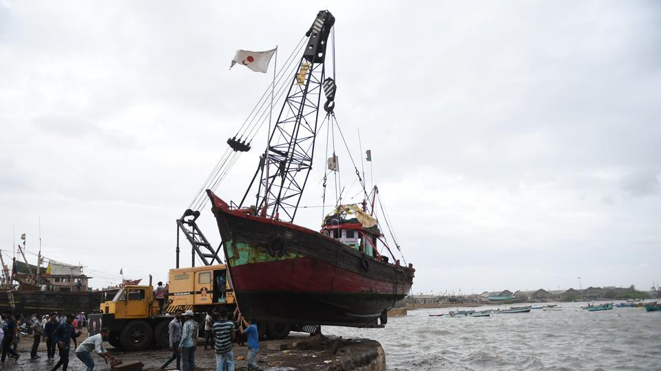 Fishermen lift a boat out of the sea as a part of precautionary measures as Cyclone Vayu nears the coastline at Veraval Port. Veraval is a major hub of India's fisheries industry exporting to Japan, South East Asia, Europe, the Gulf and the United States. All ports in the state of Gujarat have stopped accommodating berths for ships starting Wednesday. Gujarat is home to two other major ports--Deendayal and Adani in the Gulf of Kutch. (Sam Panthaky / AFP)