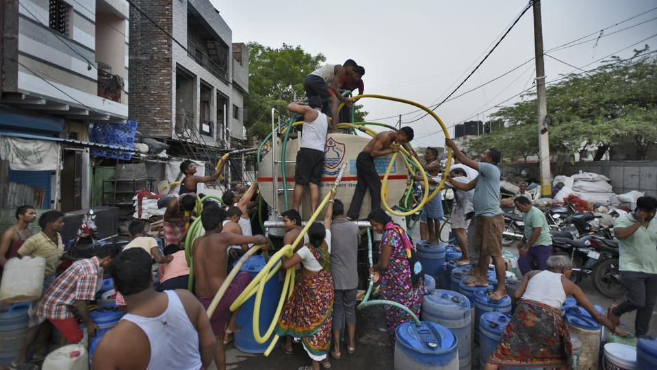 People fill their empty containers with water using lengths of hose pipe from a Delhi Jal Board tanker, at Sanjay Colony in Okhla Phase II, in New Delhi. The tankers arrive between 6 am and empty out by 7am, when everyone rushes at them to fill their buckets which often result in arguments and fights. The morning hours are most crucial to fill water as many residents head out to work during the day. (Burhaan Kinu / HT Photo)