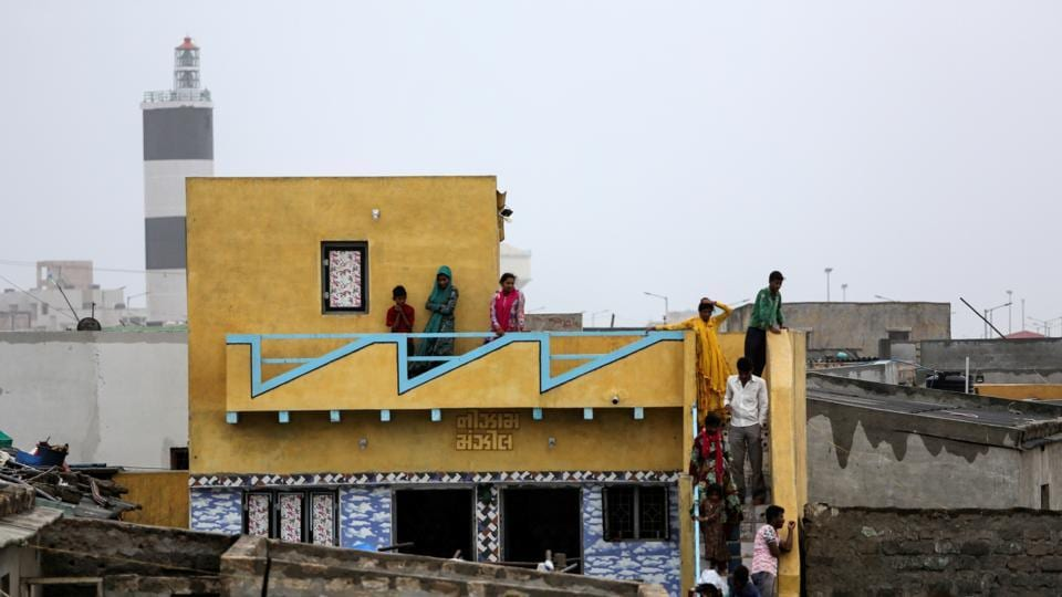 Residents watch high waves from their house ahead of Cyclone Vayu in Veraval. Operations at airports in Porbandar, Diu, Bhavnagar, Keshod and Kandla are ceased till Thursday midnight. The railways has cancelled 77 trains and short terminated 33 others. (Amit Dave / REUTERS)