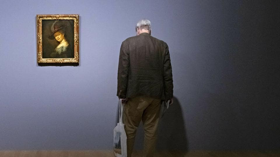 A visitor stands besides the painting 'Bust of a young woman smiling (Saskia van Uylenburgh)' (1633) by Rembrandt during a press preview of the exhibition 'Rembrandt's Mark' in Dresden, Germany. The exhibition presents about 100 works from Rembrandt's entire career in dialogue with about 50 etchings and drawings of selected contemporaries and later artists.  (Jens Meyer / AP)