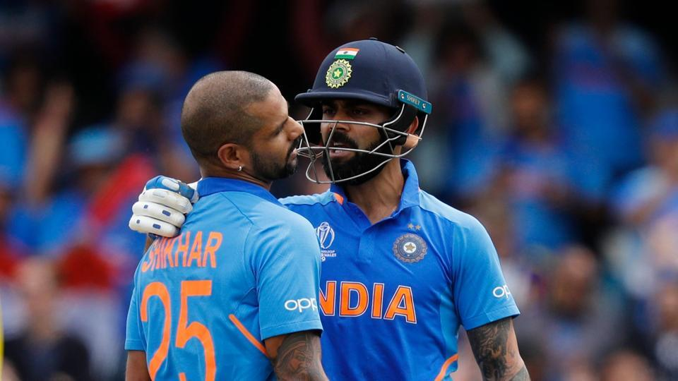 India's Shikhar Dhawan (C) celebrates after scoring a century (100 runs) alongside India's captain Virat Kohli (R) during the 2019 Cricket World Cup group stage match between India and Australia at The Oval in London on June 9, 2019.