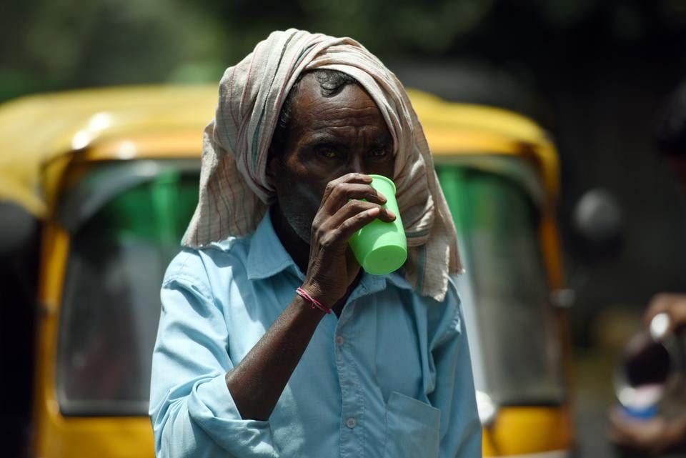 A man drinks from a glass of sweetened rose milk offered to passersby to beat scorching temperatures on the occasion of Ekadashi at Safdarjung Enclave in New Delhi, India, on Thursday, June 13, 2019