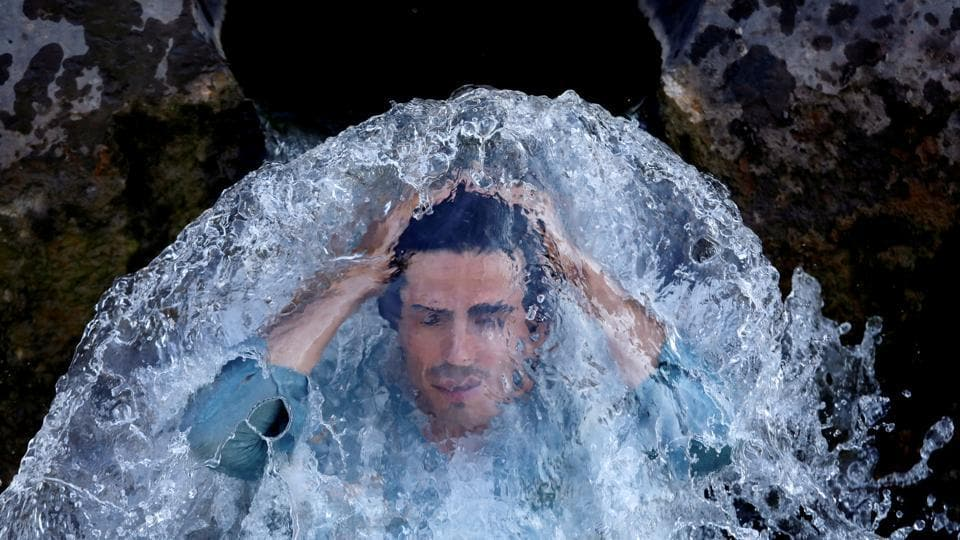 A man cools off under a water pipe from a canal on the outskirts of Peshawar, Pakistan. (Fayaz Aziz / REUTERS)