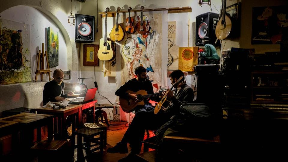 "Two men play their guitars during a jam session at the Tejo Bar in Lisbon. ""Inspiration for my new record all started here in Lisbon, at Tejo Bar,"" Madonna said on Instagram, of her Madame X album, which released yesterday.  (Patricia De Melo Moreira / AFP)"