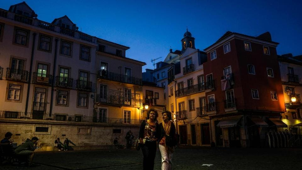 Two tourists take a walk at the Alfama neighbourhood in Lisbon. Critics have rated Madame X as Madonna's most bizarre album yet, but also one, that by virtue of embracing Latin pop, has made her sound more natural than she has in a while.  (Patricia De Melo Moreira / AFP)