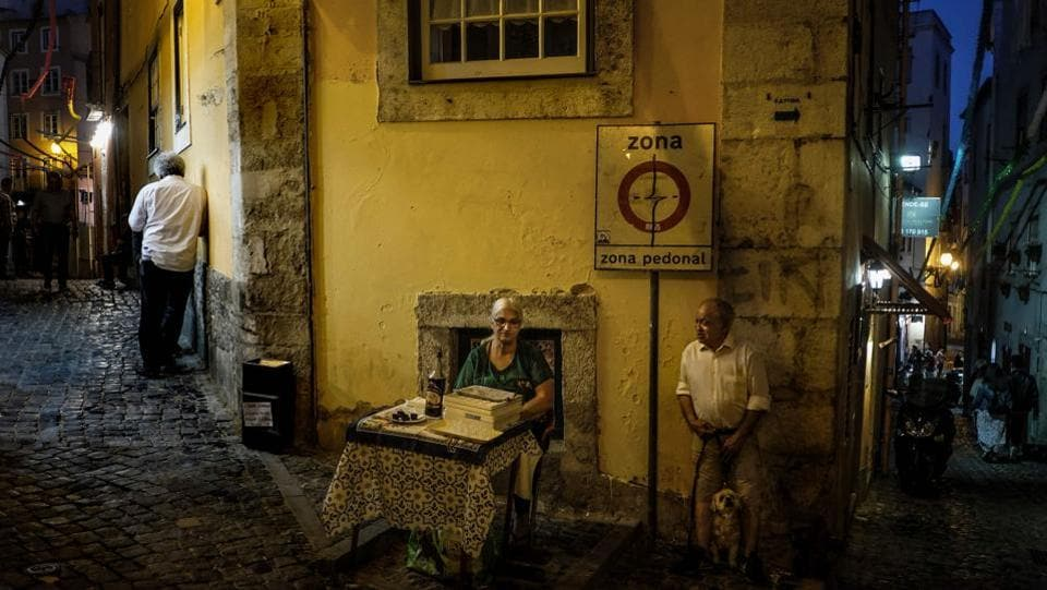An Alfama resident (C) sells