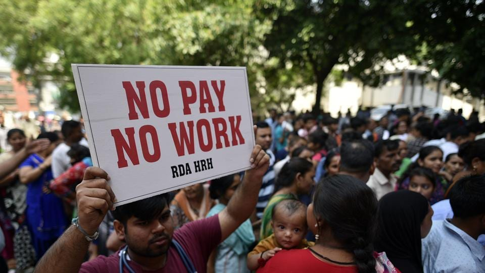 Doctors from Hindu Rao hospital holdup placards while on an indefinite strike demanding the release of 3 months' salary, at Malka Ganj in New Delhi, India, on Monday, May 20, 2019.