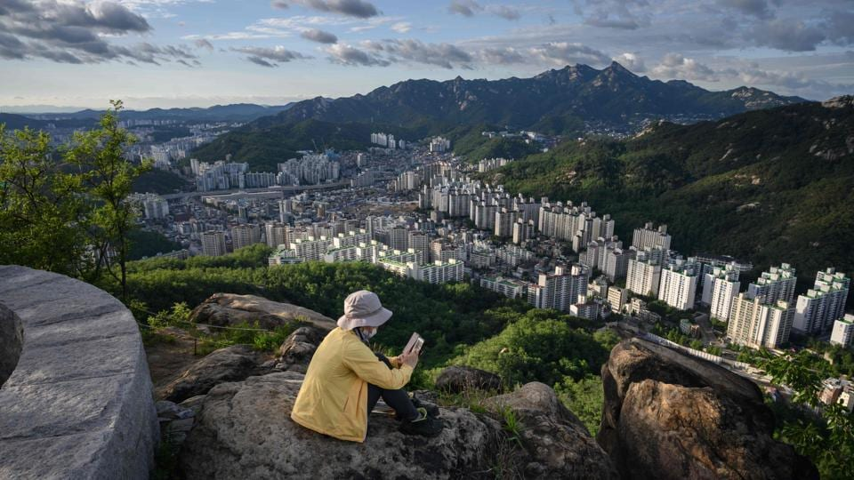 A  woman looks at her phone, sitting on top of rocks from where the Seoul skyline can be seen in the background in South Korea. (Ed Jones / AFP)