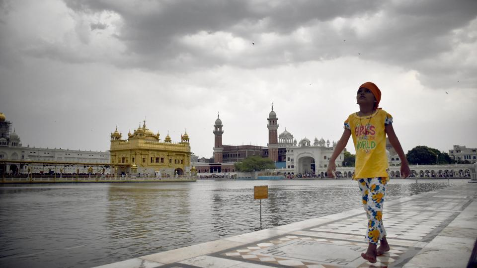 A girl circumambulates the Golden Temple as dark clouds loom over it, in Amritsar, Punjab. (Sameer Sehgal / HT Photo)