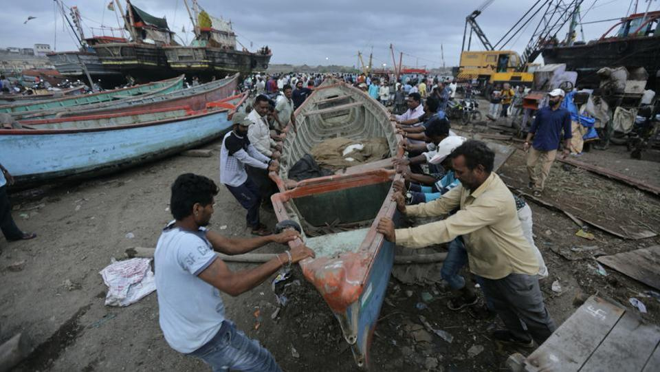 People move a fishing boat to a safer ground on the Arabian Sea coast in Veraval, Gujarat. The authorities evacuated tens of thousands of people as a severe cyclone in the Arabian Sea approached the western state of Gujarat, lashing the coast with high winds and heavy rainfall. (Ajit Solanki / AP)