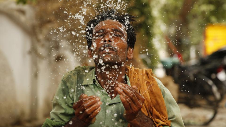 A worker splashes water on his face to cool himself on a hot afternoon at Prayagraj, Uttar Pradesh. (Rajesh Kumar Singh / AP)