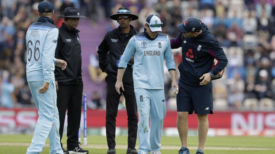 England's captain Eoin Morgan, second right, hobbles off the field of play with an injury