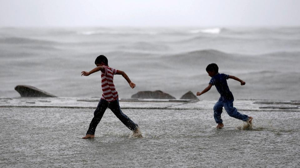 Children play in a puddle of water as it rains at a sea front in Kochi, Kerala. (Sivaram V / REUTERS)