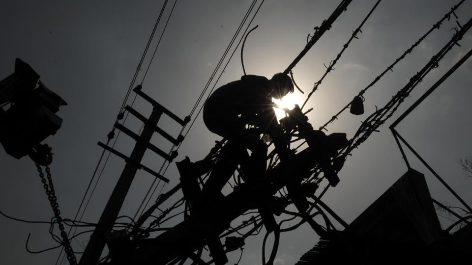 """Basant Yadav fixes power lines on MG Road. Yadav, a native of Darbhanga in Bihar, is currently an employee of an electricity distribution company in Gurugram. """"When you are working on top of the pole, the sun hits you directly. I sometimes get blackouts, so I pause for a minute. But not working is not an option for me,"""" he said. Several such workers are braving the heat to make a living in the city.  (Parveen Kumar / HT Photo)"""