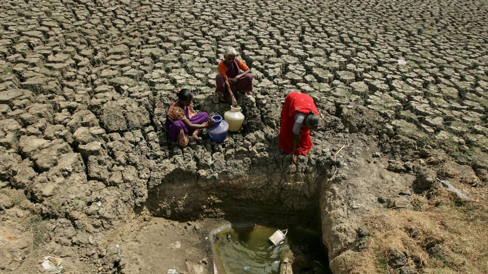 Women fetch water from an opening made by residents at a dried-up lake in Chennai, Tamil Nadu. (P. Ravikumar / REUTERS)