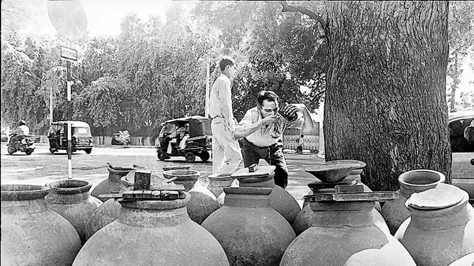 A man quenches his thirst from a pitcher by the roadside. Such pitchers were a common sight across Delhi until the 1990s.