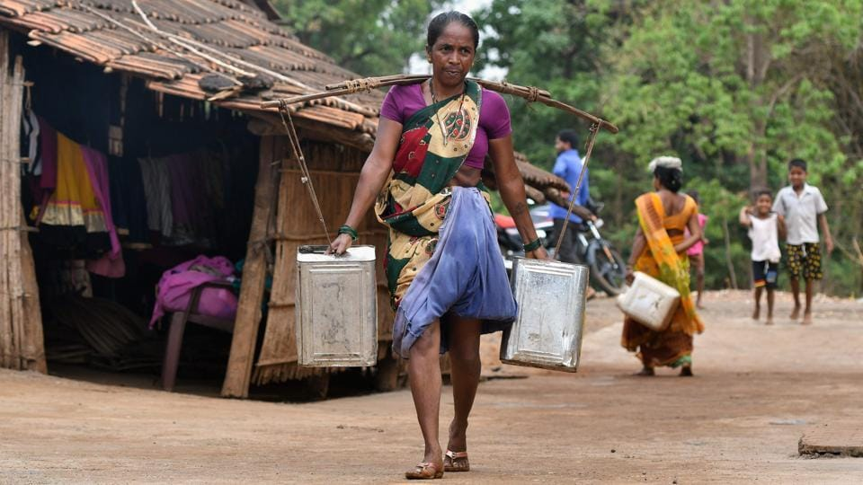 "A woman carries water in stainless steel cans at Shakar Pada village. The tanker operators come back, fill up and head out again. Often Dukre doesn't finish his rounds until 7.30 pm. ""It's hard work but my heart feels good because I am helping people,"" he said. (Punit Paranjpe / AFP)"