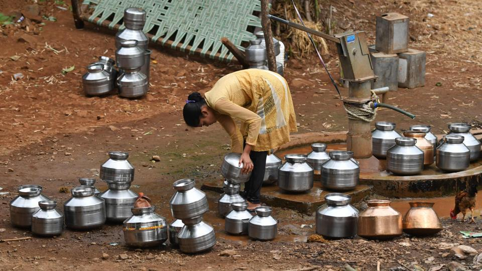 A woman fills stainless steel pots with water. India's hot season has been particularly harsh this year, with temperatures rising above 50 degrees Celsius in Rajasthan. Almost half of India -- an area home to more than 500 million people -- is facing drought-like conditions because of deficient pre-monsoon rainfall, according to the Indian Meteorological Department (IMD). (Punit Paranjpe / AFP)