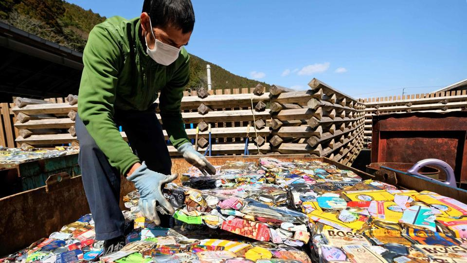 """A worker stacks sheets of compacted aluminium cans at a waste centre in the town of Kamikatsu, Tokushima prefecture. """"Yes, it's complicated,"""" said Naoko Yokoyama, a 39-year-old resident who had brought her trash to the waste centre. """"But I have become more environmentally conscious since I moved here a year ago,"""" she told AFP. (Kazuhiro Nogi / AFP)"""