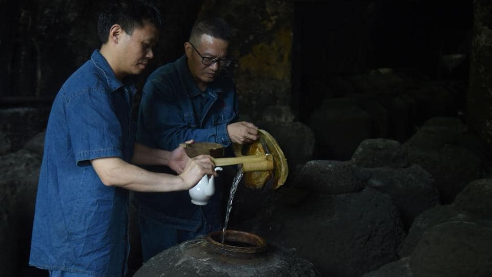 "Workers inspect a container filled with baijiu liquor in a cave located in the hills of Luzhou. A wave of ""baijiu bars"" opened in China, the US, and Europe in recent years as a buzz swelled. But many have since closed. ""It's a challenge for the customers. It hasn't really caught on in the West yet,"" said Demon, Wise & Partners owner Paul Mathew. (Hector Retamal / AFP)"
