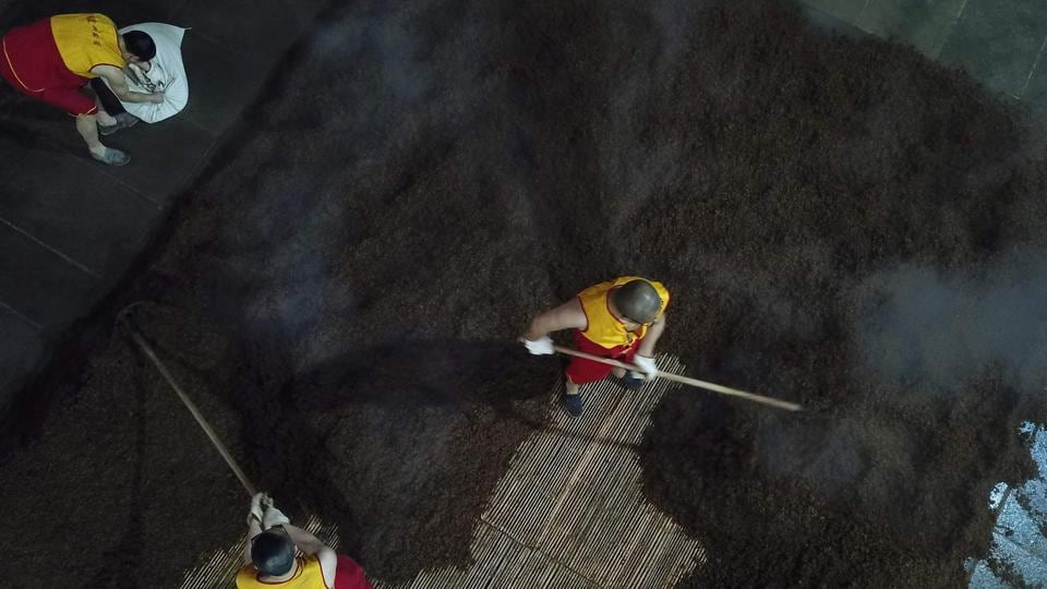 "Workers prepare grain on a work floor. Baijiu has been on a roller-coaster in recent years. A government corruption crackdown launched in 2012 hit hard: premium brands had become the go-to gift for bribing Communist officials. Sales fell off a ""cliff,"" Su said. And many younger Chinese, exposed to French wine and German beer, shun a rotgut they equate with rural regions and drunken businessmen. (Hector Retamal / AFP)"