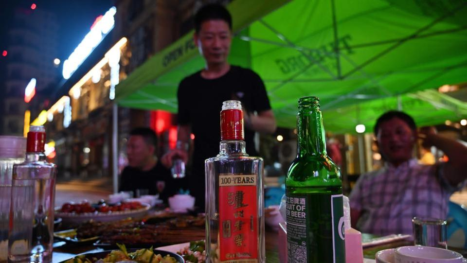 "A bottle of baijiu liquor on a table while people enjoy dinner at a restaurant. Jim Boyce, a Beijing blogger on China's booze scene who launched August 9 ""World Baijiu Day"" in 2015, said baijiu is hampered by how it's consumed in China: straight up, with food. ""The fact is, people, at least in North America and Europe, don't drink lukewarm straight 52% alcohol,"" he said. (Hector Retamal / AFP)"