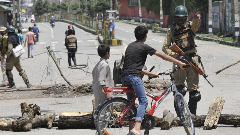 A paramilitary soldier diverts children from a barricade during restrictions in downtown Srinagar, Jammu and Kashmir. Image used for representational purpose only.