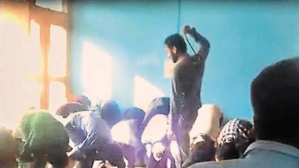 A video grab of the teacher thrashing students in a school in Doda district.